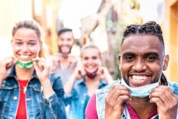 Multiracial friends with face mask after lockdown reopen - New normal friendship concept with guys and girls having fun together on travel vacation
