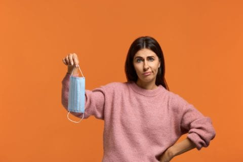 Dissatisfied young female holds medical mask. looks sadly at camera. does not want to use it. wears in pink knitted sweater isolated over orange.