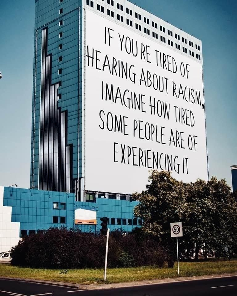 An image of a building with a huge digitally rendered sign on it reading if you're tired of hearing about racism imagine how tired some people are of experiencing it.