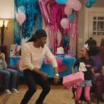 An image of a Black family happily celebrating. A little girl is dancing with a young adult man.
