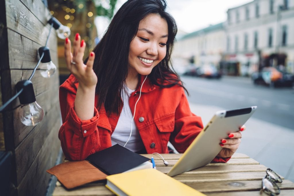 Young good looking Asian brunette in red denim jacket reading amusing news on social media on modern tablet and smiling while enjoying free time in outdoor cafe.