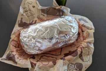 Palm Springs, California, United States - October 27, 2018: Chipotle Mexican Grill burrito wrapped in tin foil in a basket with Tabasco sauce.