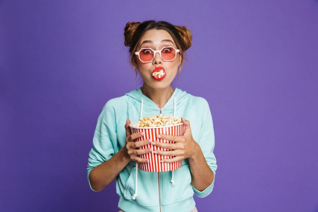 Portrait of a cute young girl with bright makeup isolated over violet background, eating popcorn.  Generic photo for mention of Separation and Jupiter's Legacy.