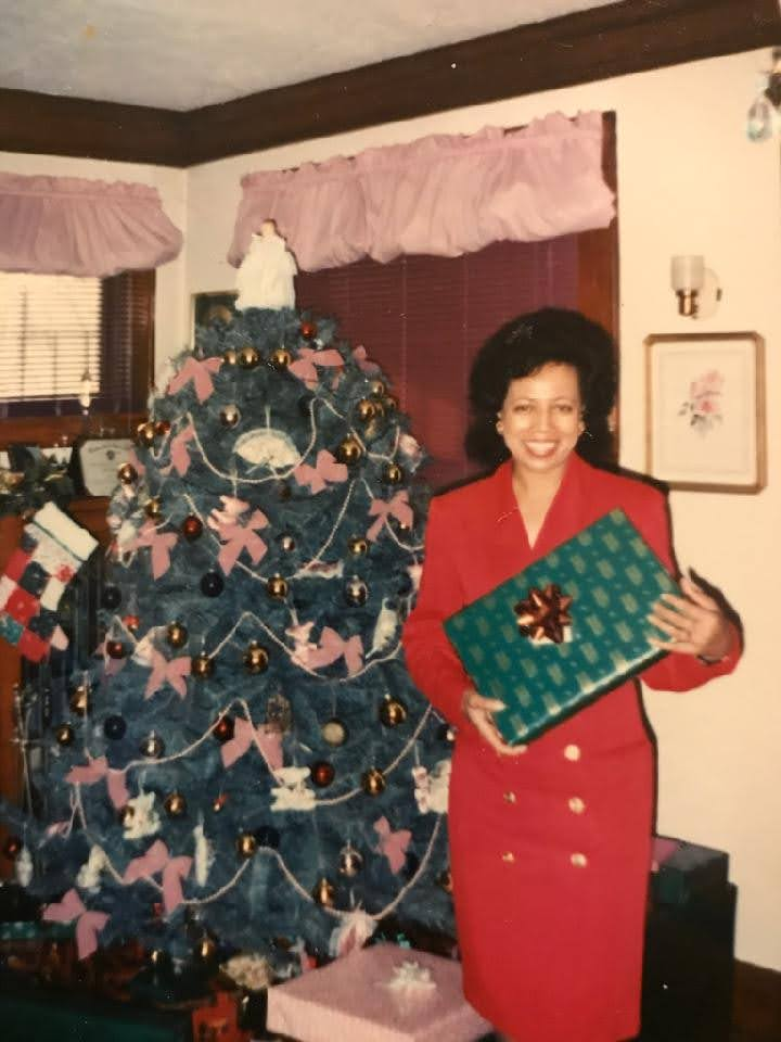 My mom standing in front of a Christmas tree holding a gift