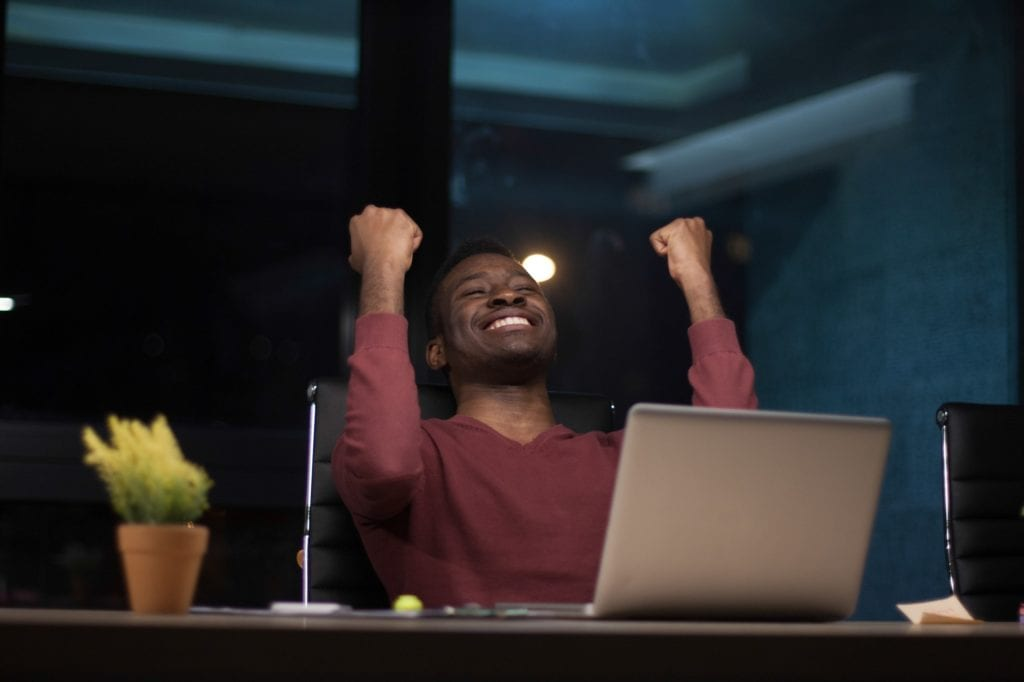 Smiling young business owner is working at his desk on his laptop
