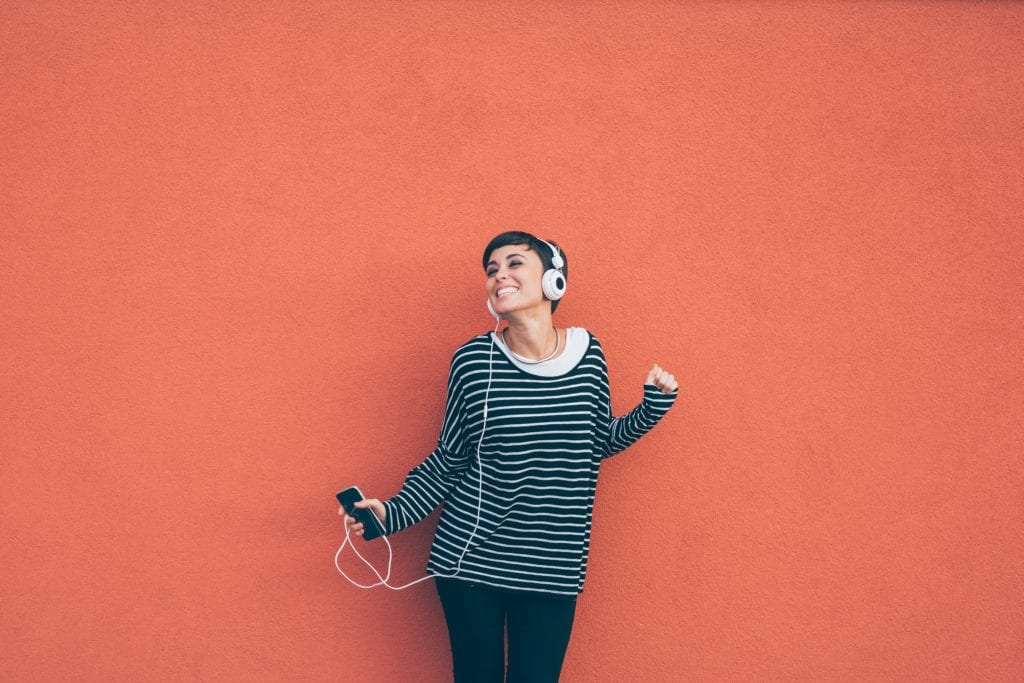 Knee figure of young beautiful caucasian woman listening music with headphones and smart phone hand hold, dancing, eyes closed smiling, leaning on a orange wall - music, happiness, technology concept