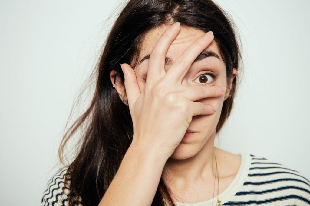 A woman partially covering her face with her hand - meant to symbolize unease.