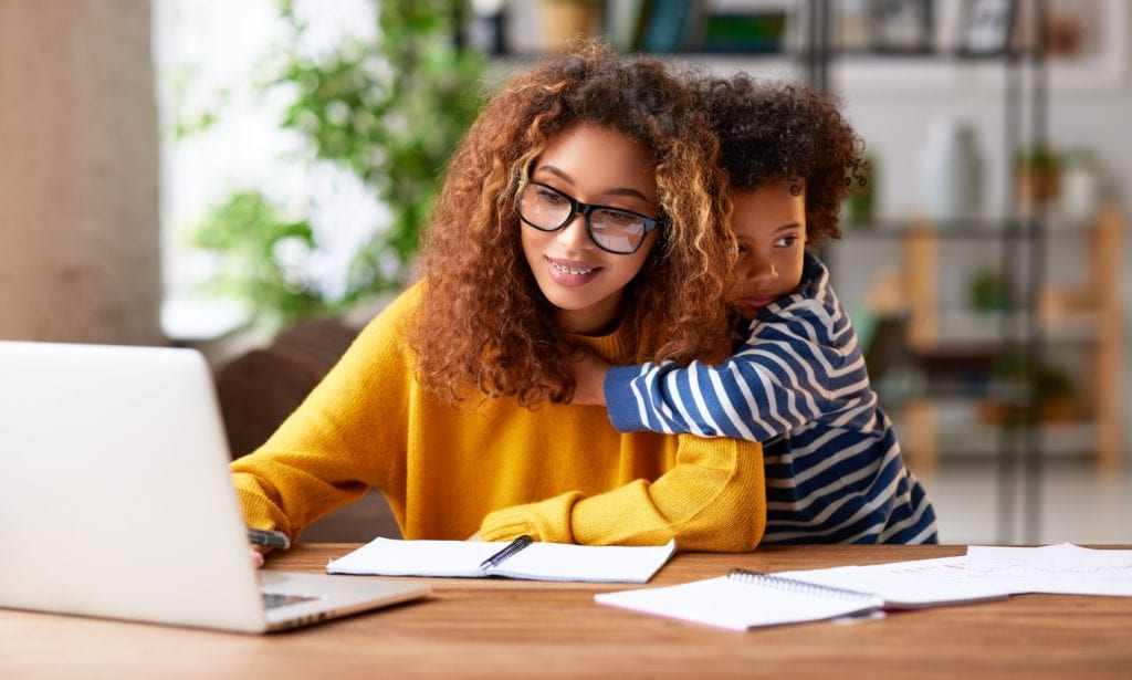 Working with kids. Young focused woman mother wearing eyeglasses using laptop and thinking about work task while small boy son gently hugs her.