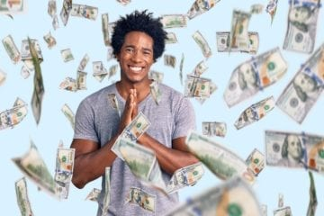 Handsome African American man with afro hair wearing casual clothes praying with hands together asking for forgiveness smiling confident while being showered with falling hundred dollar bills.