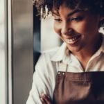A close-up head shot of an attractive female server in a brown apron.