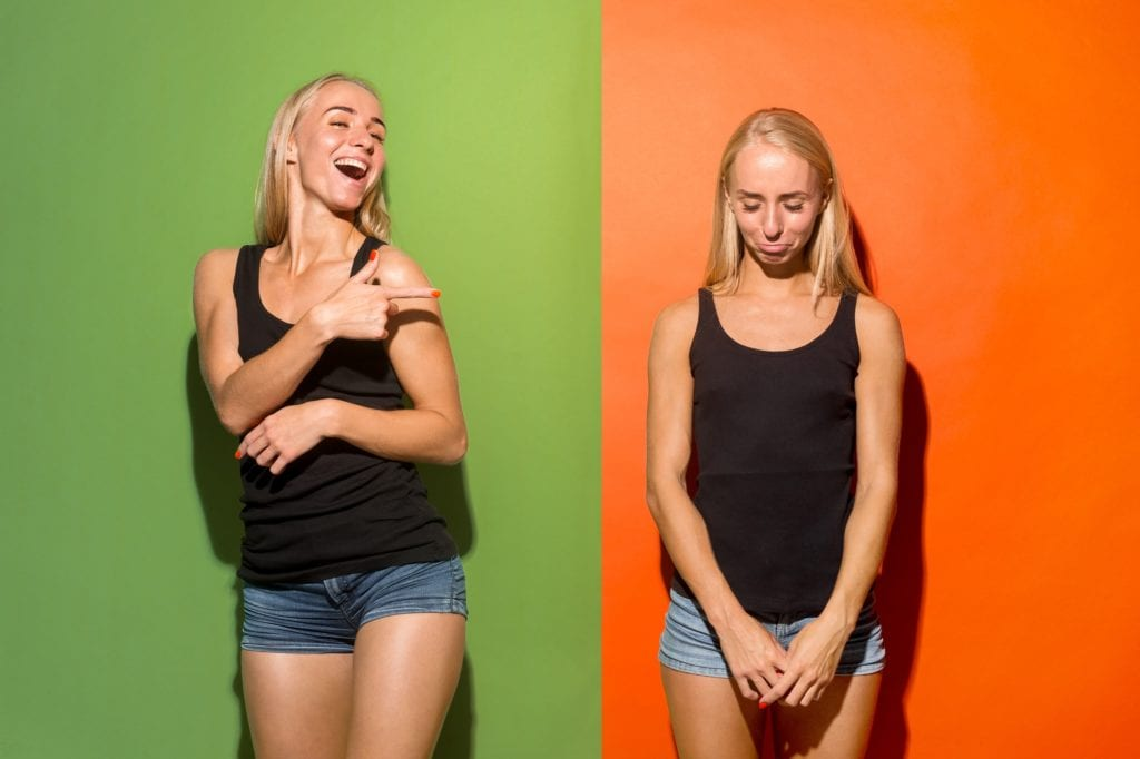 A woman laughing at a sad version of herself that she's standing next to.  Meant to symbolize overcoming yourself.