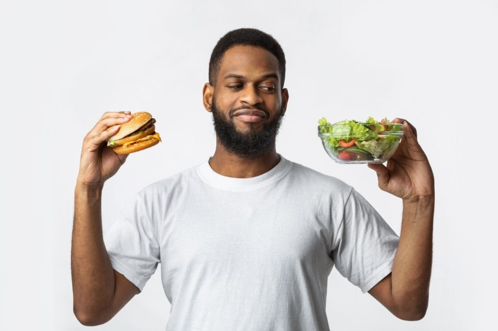 Food Choice. Hungry Black Guy Holding Burger And Vegetable Salad Choosing Diet Standing On White Studio Background. Healthy Vs Unhealthy Nutrition, Junk Food Concept