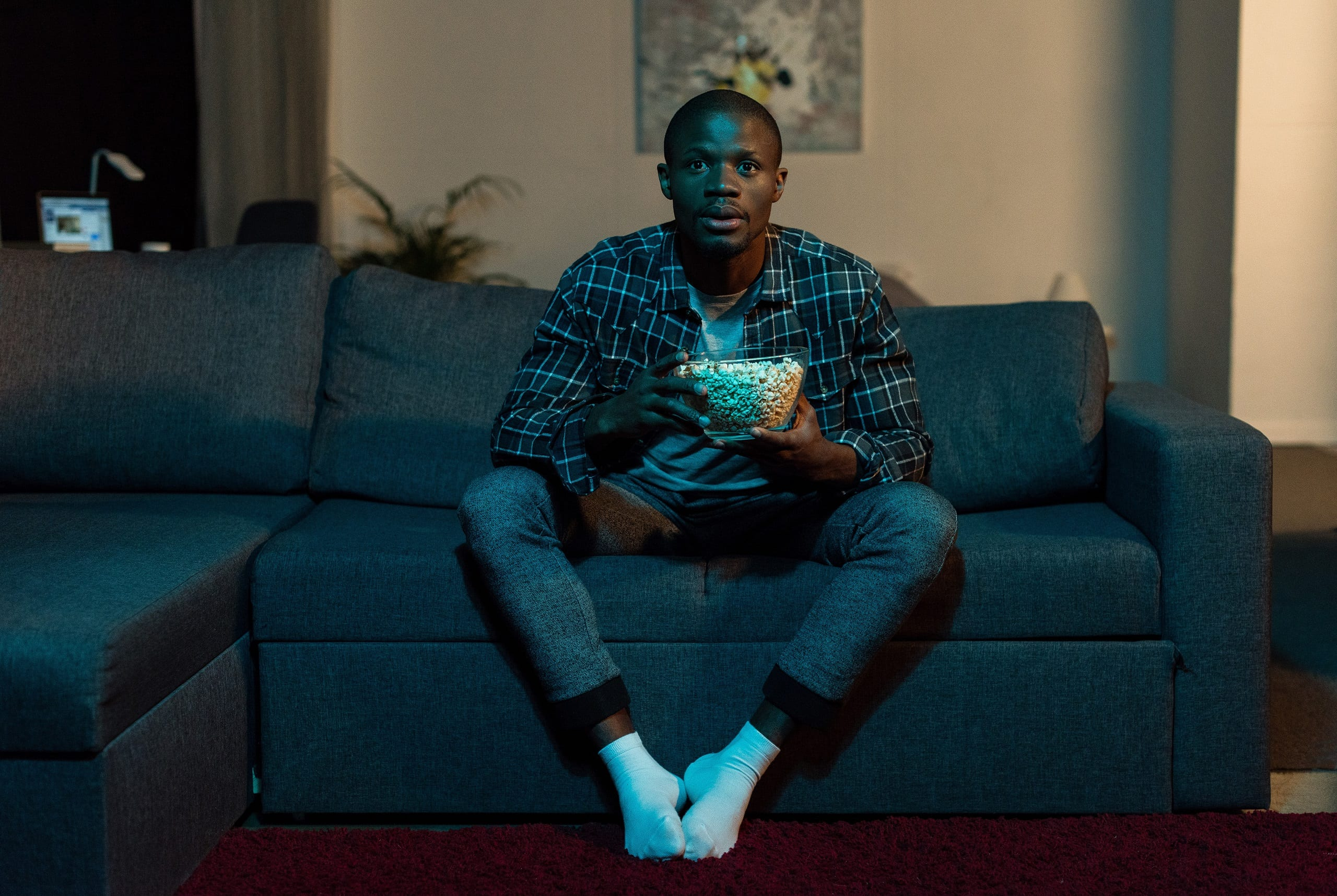 concentrated african american man with popcorn in hands watching tv at home