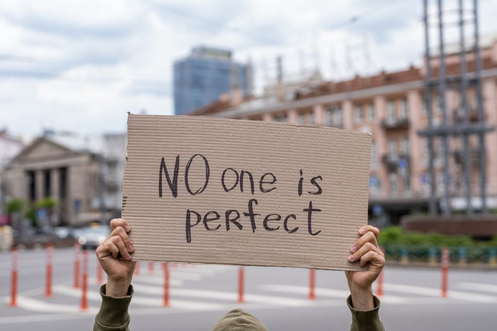 No one is perfect. Positive thinking phrase support and friendly wish. manifest parade. Guy with sign inspiration.