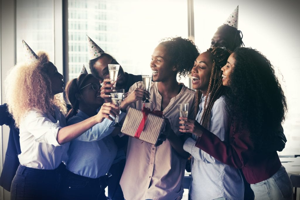 Happy multiethnic colleagues have fun congratulate coworker with happy birthday at party in office. Overjoyed diverse multiracial employees celebrate anniversary cheers clink glasses at workplace.