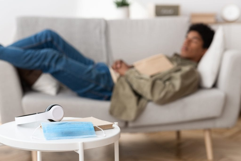 Blurred black teenage guy lying on sofa at home, selective focus of medical mask, book and headphones on table.