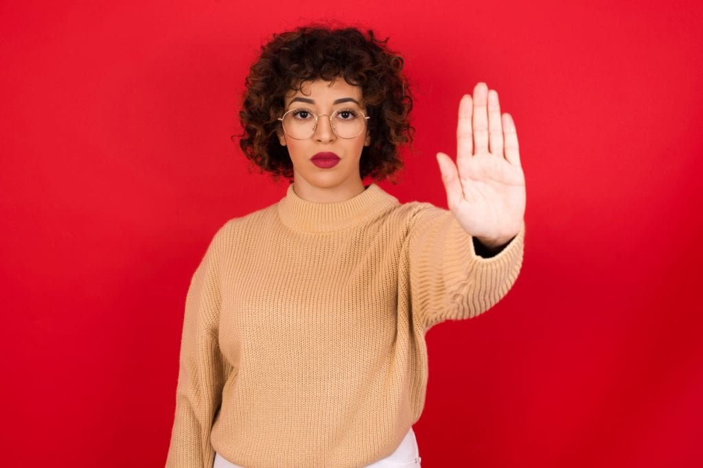 Young beautiful Arab woman wearing knitted sweater standing against red background doing stop gesture with palm of the hand. Warning expression with negative and serious gesture on the face. She is stingy.