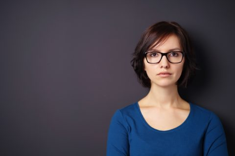 Serious Young Woman with Eyeglasses Looking Away Against Gray Wall with Copy Space on the Left Side.