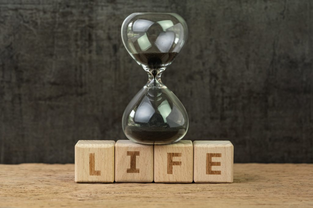 Living time for human life countdown, lifetime or retirement concept, sandglass or hourglass on wooden cube block with alphabet building the word Life on wood table, dark black background.