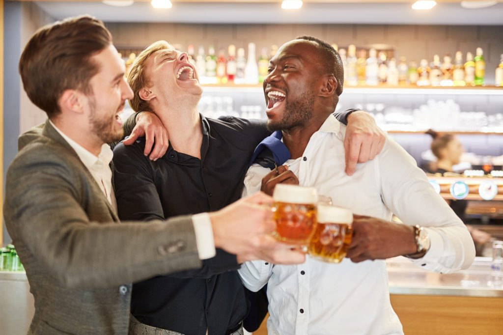Friends on a men's evening having a beer in a pub or bar.