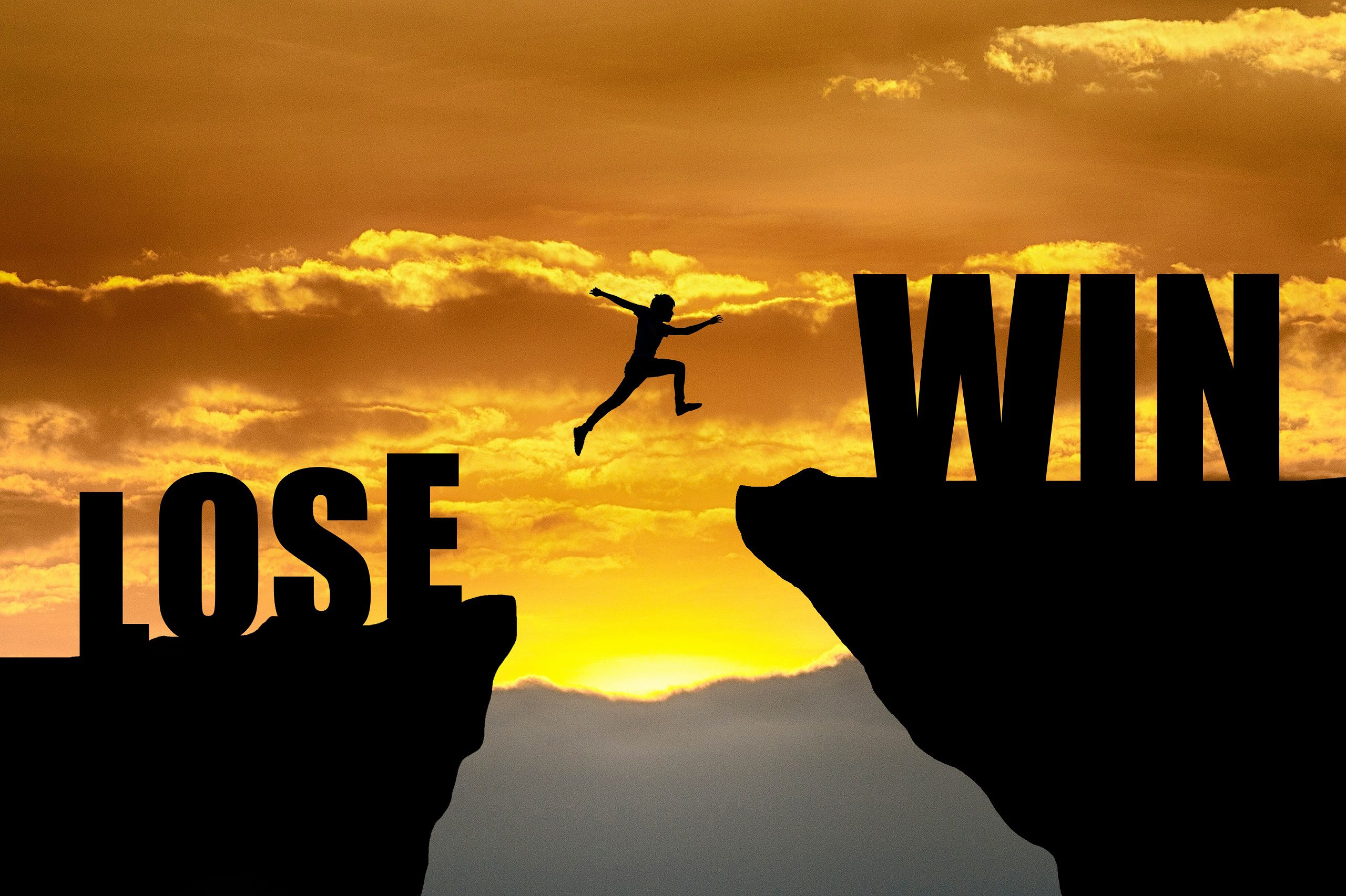 Courage businessman jumping from LOSE to WIN on sunrise background. business concept