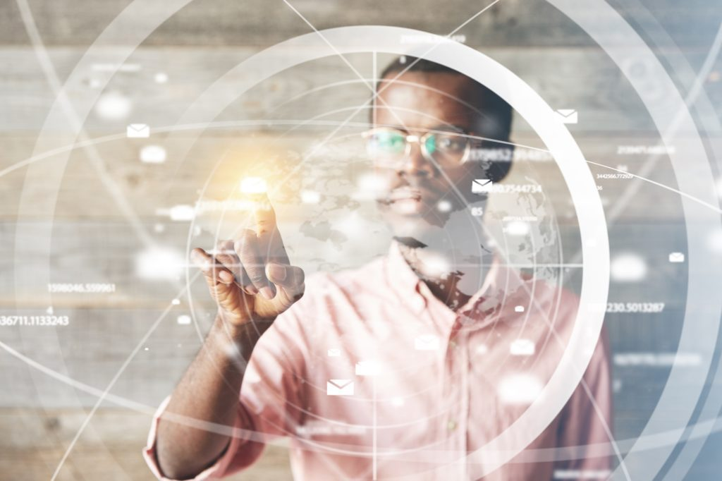 Portrait of African man in glasses, using digital device, pointing at icons on futuristic screen interface against high-tech interior, looking with serious concentrated expression. Selective focus.  Future of Technology concept.